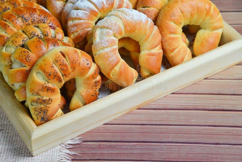 Verse enkel gebakken zoete broodjes of broodjes op dienblad voor ontbijt en thee of koffietijd op houten achtergrond royalty-vrije stock foto