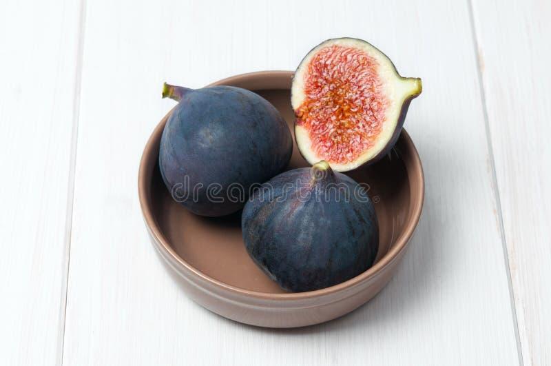 Verse fig. in ceramische kom op witte houten lijst stock afbeeldingen