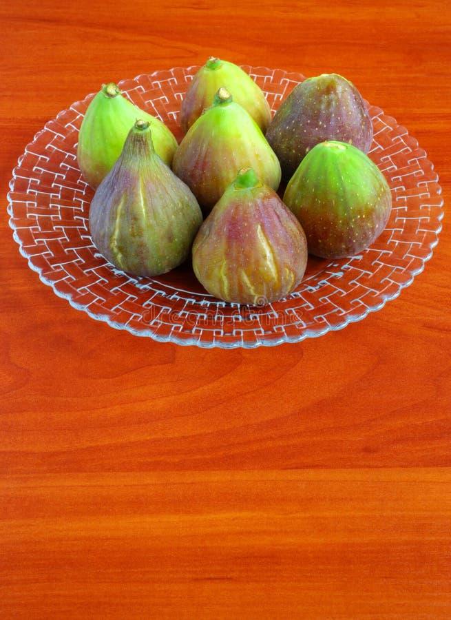 Verse fig.vruchten in plaat op houten lijst stock afbeelding