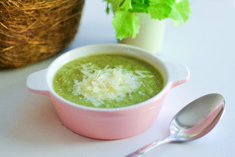 Verse fijngestampte soep met broccoli en geraspte Parmezaanse kaas in een roze plaat op een lichte achtergrond royalty-vrije stock afbeelding