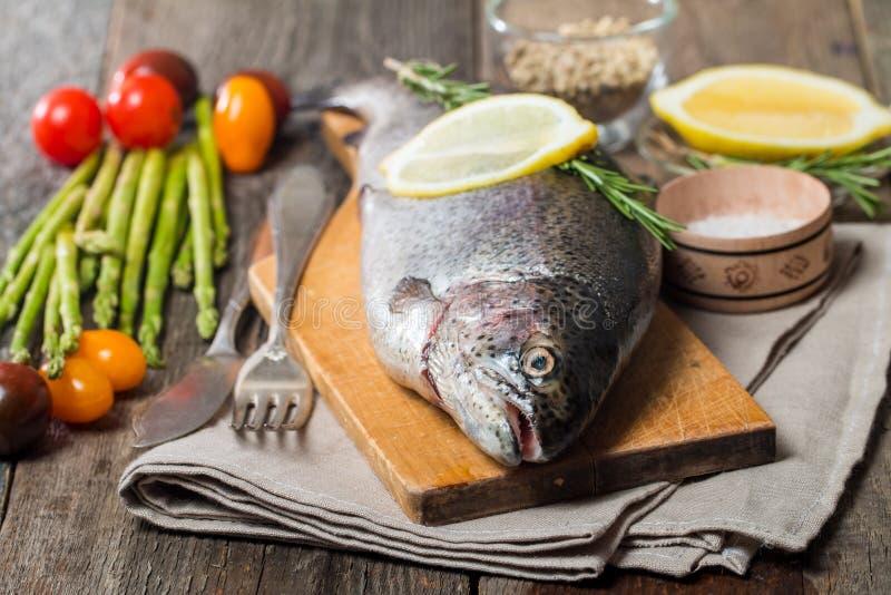 Verse forel met groenten, kruiden en kruiden stock foto's