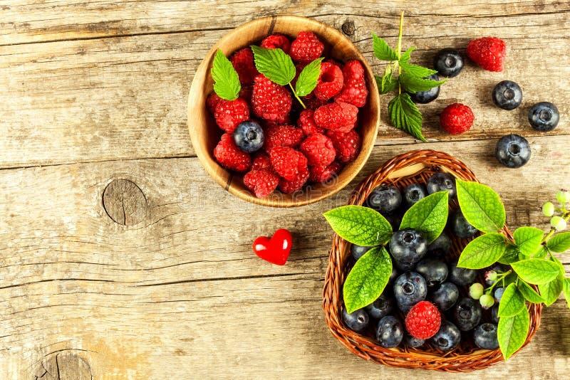 Verse frambozen en bosbessen op een oude houten lijst Fruit het plukken Gezond fruit Verkoop van bosbessen en frambozen royalty-vrije stock afbeeldingen