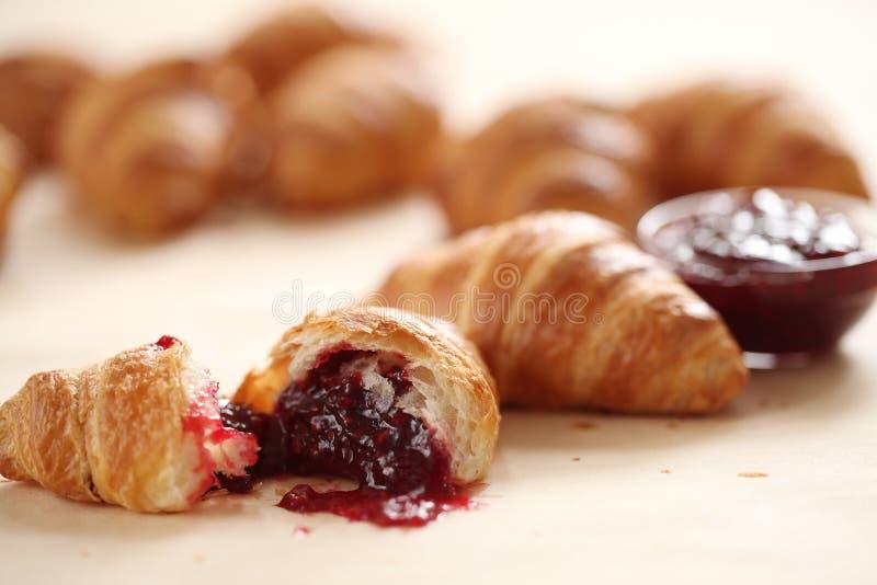 Verse Franse croissants met bessenjam stock afbeeldingen