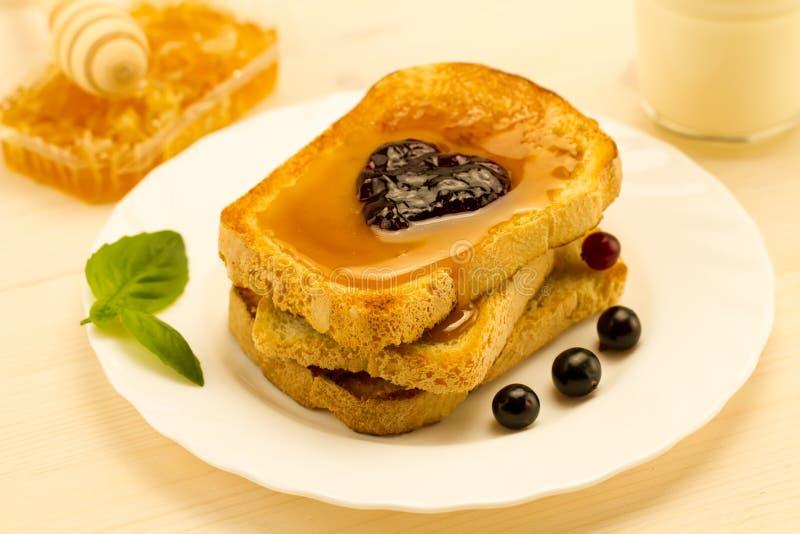 Verse Franse toost met honing en jam op een witte plaat met bessen stock fotografie