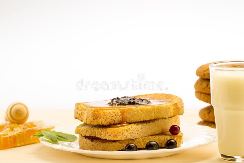 Verse Franse toost met honing en jam op een witte plaat met bessen op een witte achtergrond stock afbeeldingen