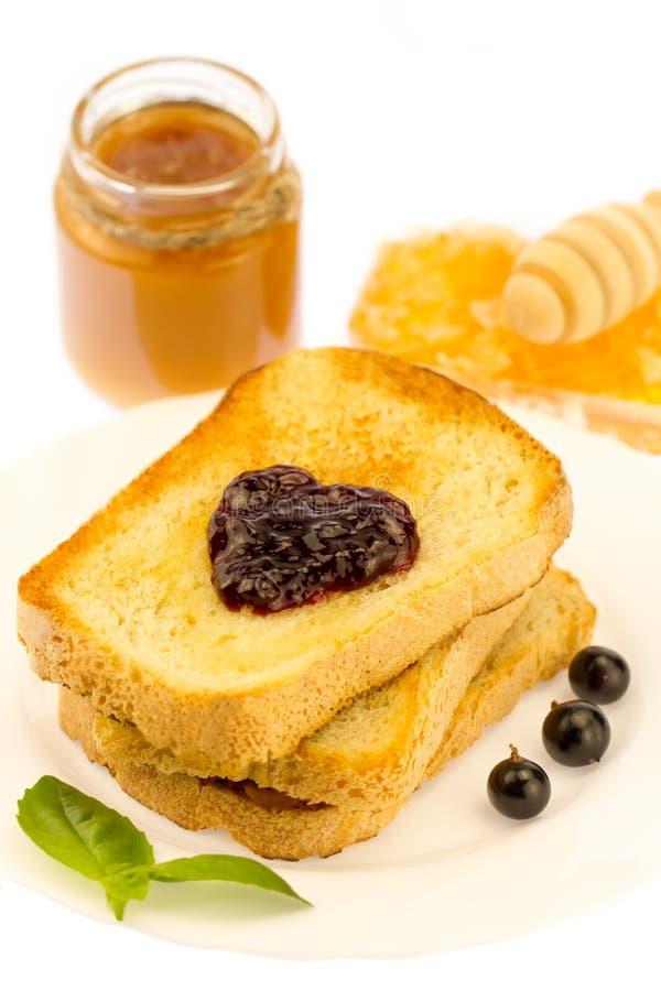 Verse Franse toost met honing en jam op een witte plaat met bessen op een witte achtergrond royalty-vrije stock afbeeldingen