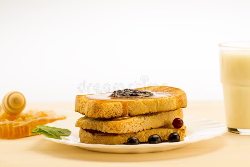 Verse Franse toost met honing en jam op een witte plaat met bessen op een witte achtergrond stock foto's