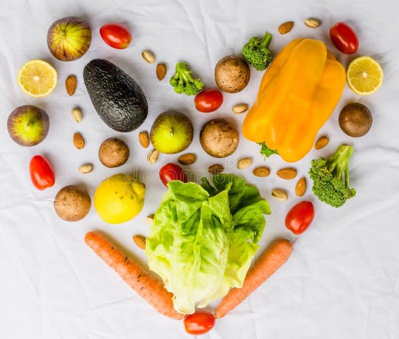 Verse fruit en groenten, korrels, en noten op een witte achtergrond in vorm van hart stock afbeeldingen