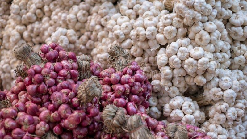 Verse garlics en de rode ondiepte verkopen bij markt stock foto