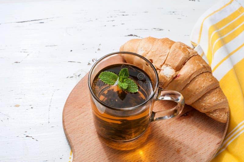 Verse gebakken croissants met thee op servet royalty-vrije stock afbeelding