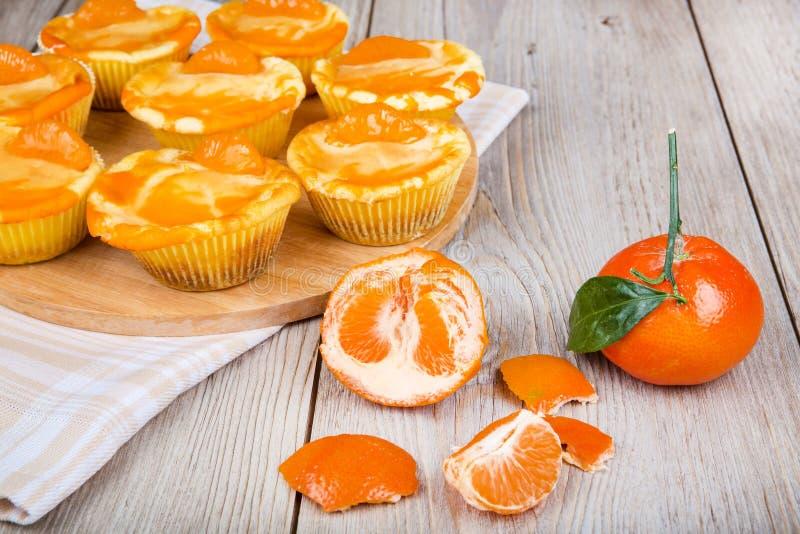 Verse gebakken miniclementinekaastaarten in muffinvormen stock foto's