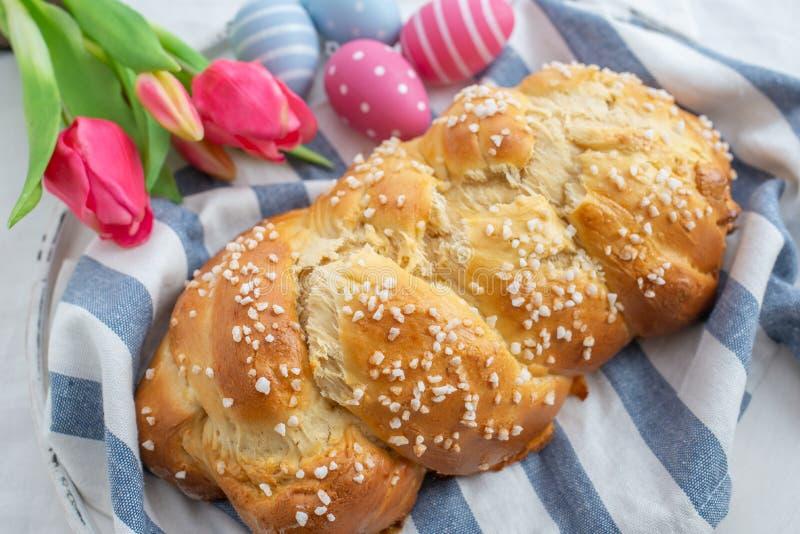 Verse gebakken smakelijke zoete brioche voor Pasen met paaseieren op een lijst stock foto