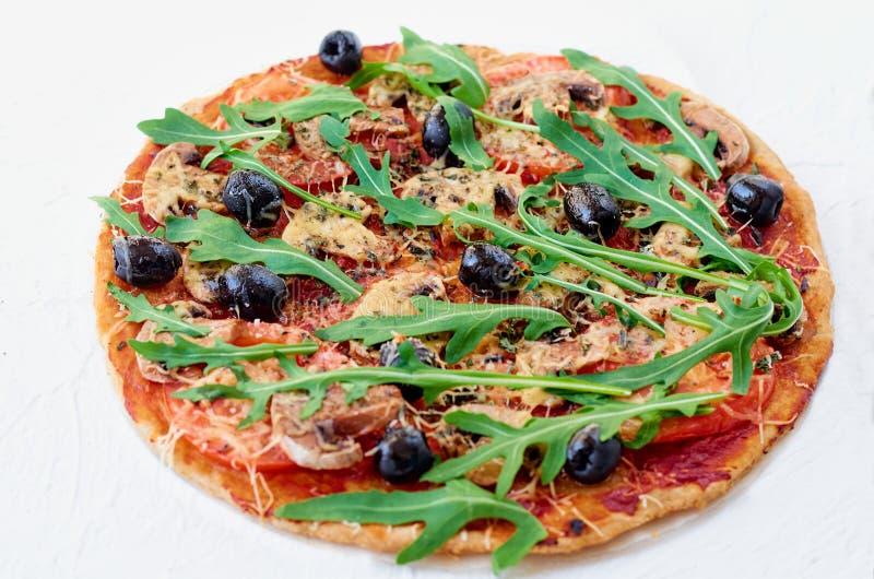 Verse gebakken vegetarische pizza met paddestoelen, tomaten, rucola, zwarte die olijven op de witte lijst worden geïsoleerd royalty-vrije stock afbeelding