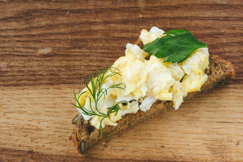 Verse gekookte roereieren met kruiden op stuk van brood, houten achtergrond stock foto