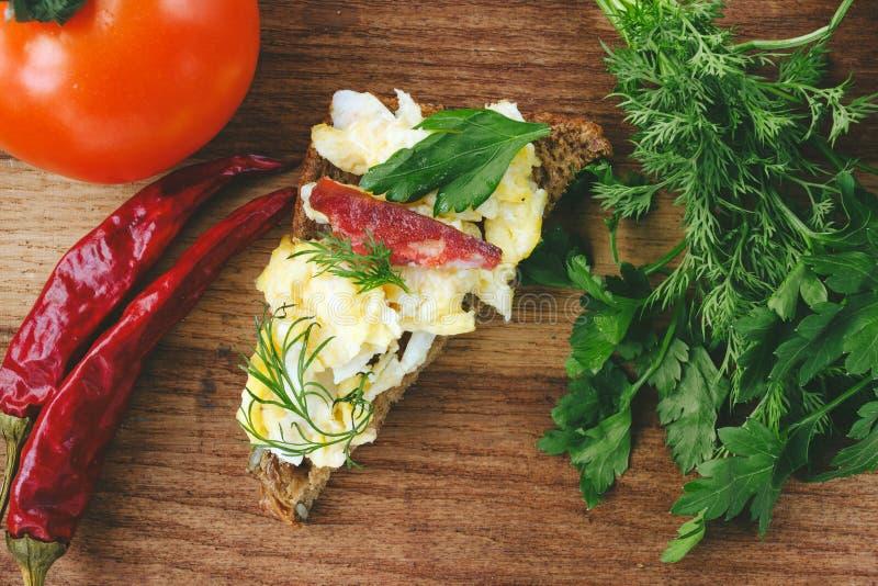 Verse gekookte roereieren met worst en kruiden op stuk van brood tomaat, Spaanse peperspeper op houten achtergrond stock foto