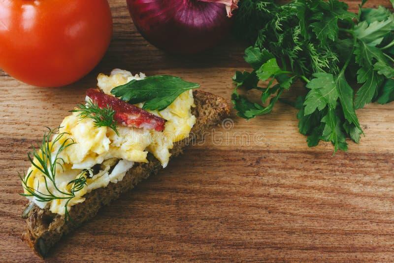 Verse gekookte roereieren met worst en kruiden op stuk van brood tomaat, ui op houten achtergrond stock afbeeldingen