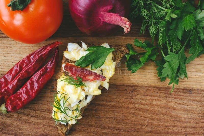 Verse gekookte roereieren met worst en kruiden op stuk van brood tomaat, ui, Spaanse peperspeper op houten achtergrond royalty-vrije stock foto's