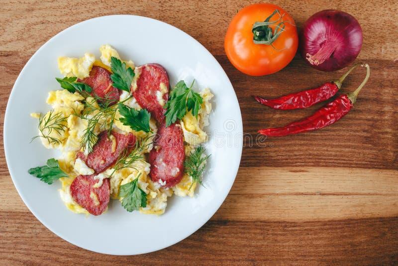Verse gekookte roereieren met worst en kruiden in witte plaat Tomaat, Spaanse peperspeper, ui op houten raads hoogste mening stock foto's