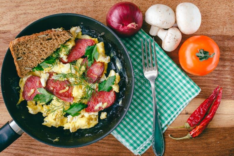Verse gekookte roereieren in pan met worst en kruiden Brood, vork, groenten, servet op houten raad, hoogste mening stock foto's