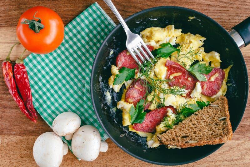 Verse gekookte roereieren in pan met worst en kruiden Tomaat, Spaanse peperspeper, paddestoelen op houten raad, hoogste mening stock fotografie