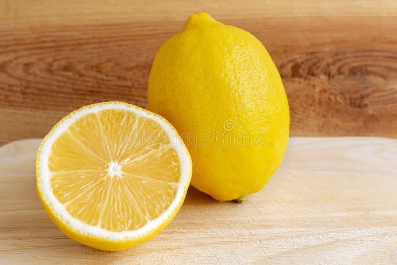 Verse gele citroen en plak van citroen op een houten lijst in de keuken stock foto's