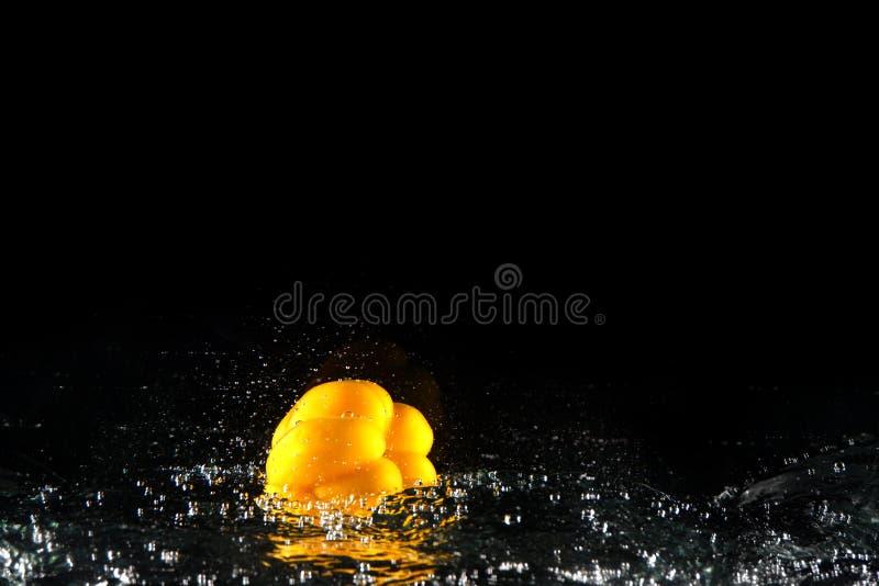 Verse Gele Groene paprika met Waterplons en Bel De ruimte van het exemplaar Sappige Gele Paprika Dropped in Water op Zwarte royalty-vrije stock foto's