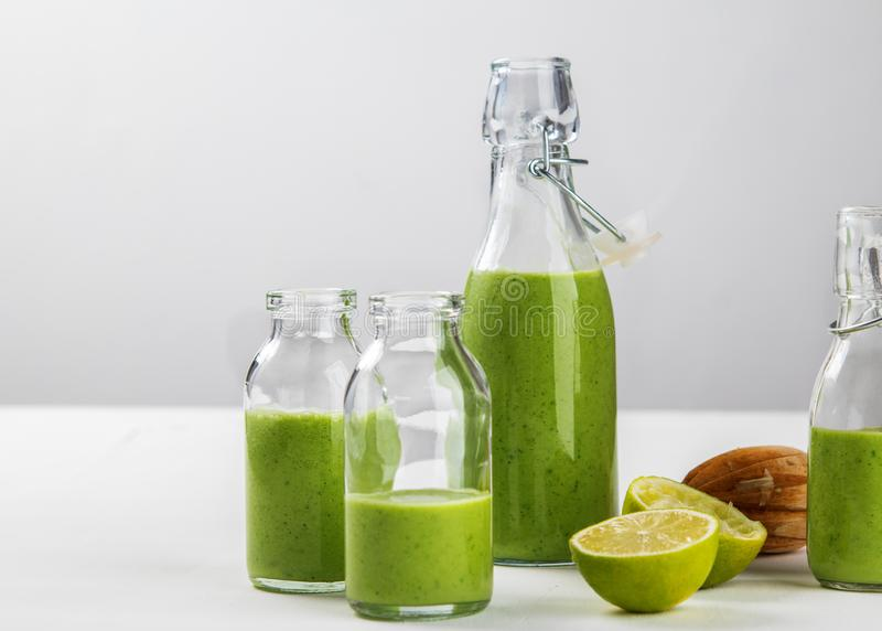 Verse gemaakte gezonde groene die smoothie in flessen op witte achtergrond wordt gediend Vruchten en groenten en zadeningrediënte stock fotografie