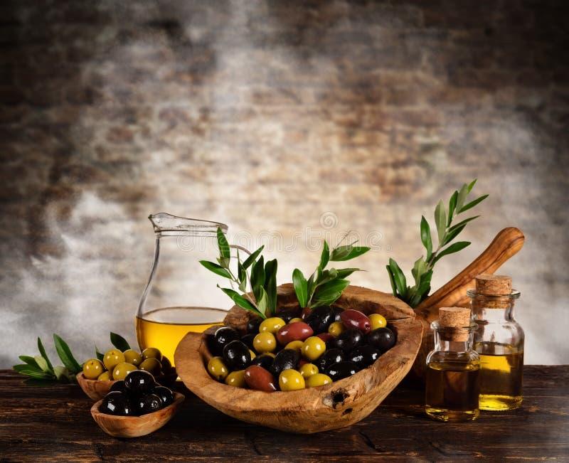Verse geoogste die olijven met olie, op houten lijst wordt geplaatst royalty-vrije stock afbeelding