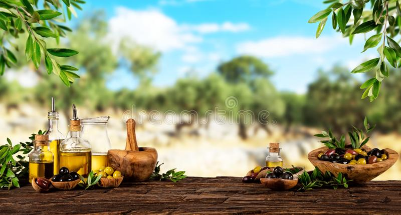 Verse geoogste die olijven met olie, op houten lijst wordt geplaatst stock afbeeldingen