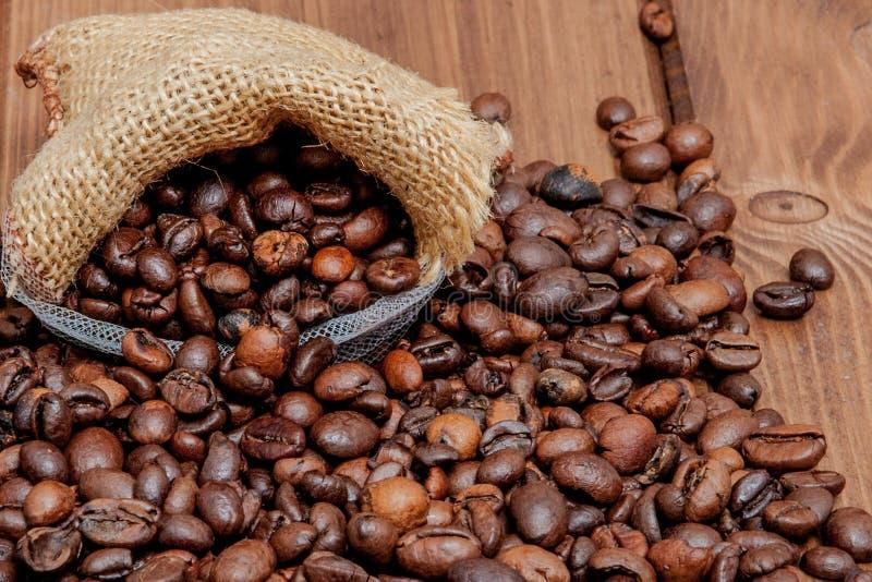 Verse geroosterde koffiebonen die de zak op de houten oppervlakte uitvallen Bruine die koffiebonen van zak op de lijst worden ver stock fotografie