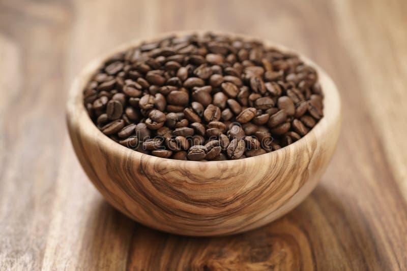Verse geroosterde koffiebonen in houten kom op lijst royalty-vrije stock foto's