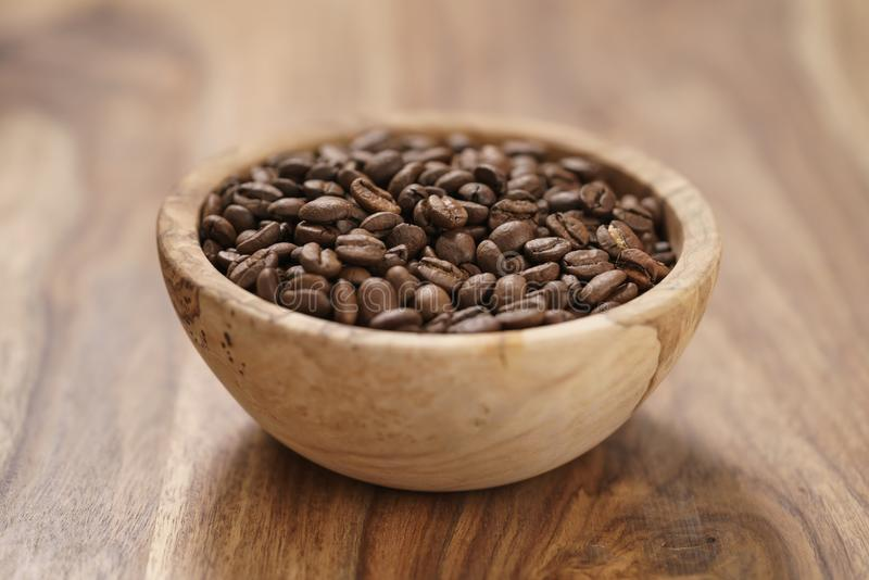 Verse geroosterde koffiebonen in houten kom op lijst stock afbeelding
