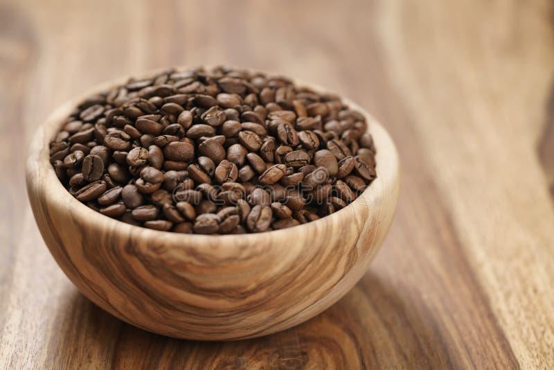 Verse geroosterde koffiebonen in houten kom op lijst royalty-vrije stock fotografie