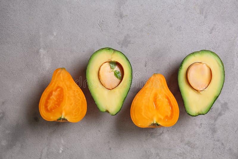 Verse gesneden avocado en tomaat op grijze geweven achtergrond royalty-vrije stock foto's