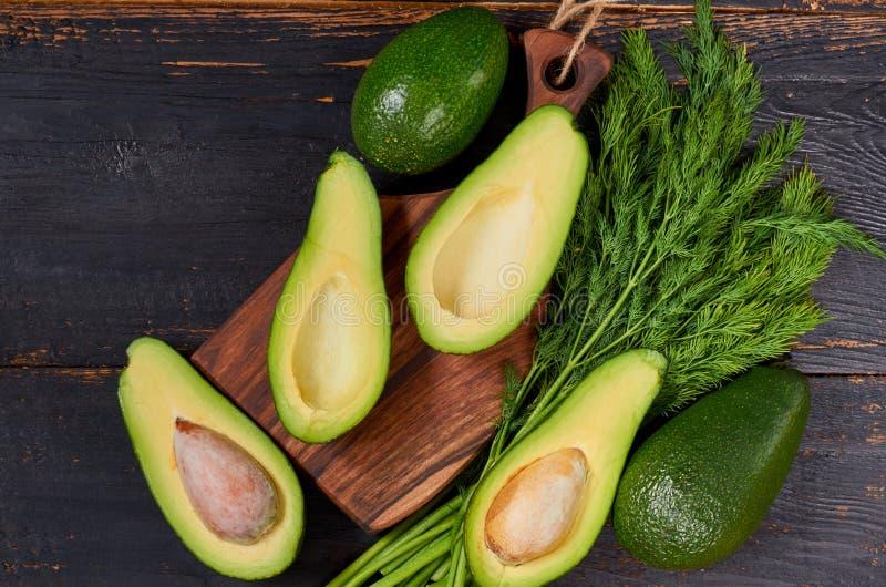 Verse gesneden avocado's en dille op de houten raad Ruwe ingrediënten voor veggie gezonde of dieetschotel op de zwarte achtergron royalty-vrije stock foto's
