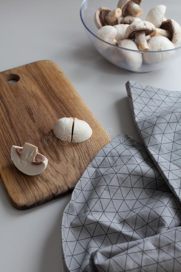 Verse gesneden paddestoelen bij houten scherpe raad Hakkende voedselingrediënten Voedselachtergrond van verse champignons stock afbeelding