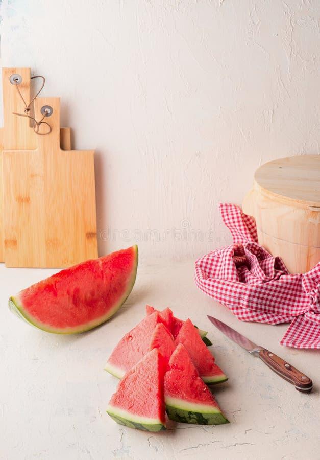 Verse gesneden watermeloen op witte lijst bij muurachtergrond met mes Sappig verfrissend de zomervoedsel De ruimte van het exempl stock foto's