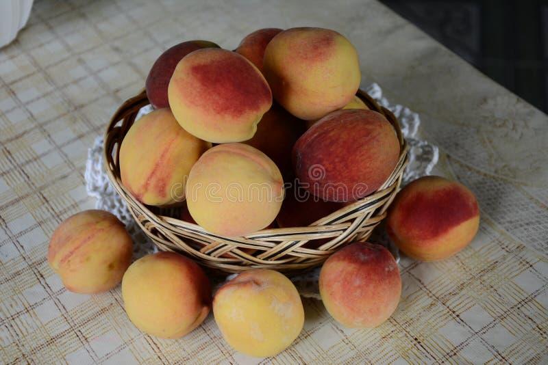 Verse geurige en zoete perziken in de mand stock afbeeldingen