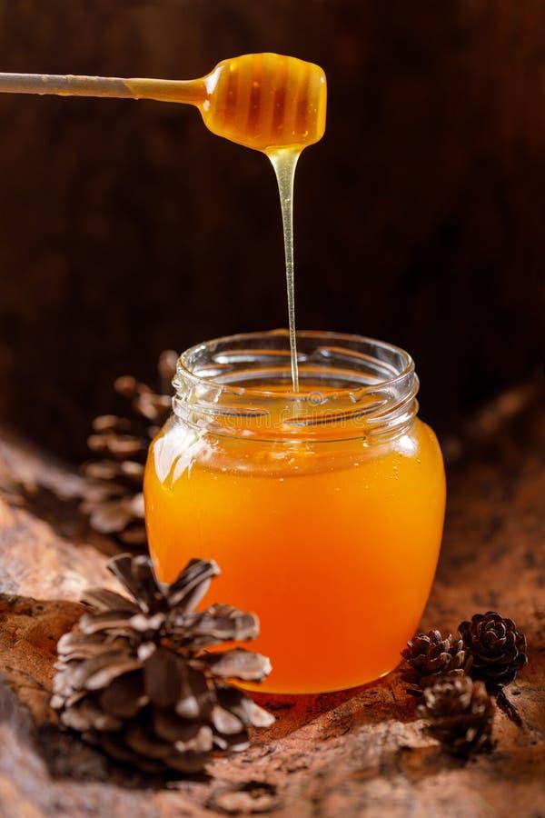Verse geurige honing die in een mooie glaskruik stromen met een houten lepel royalty-vrije stock foto
