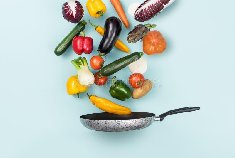 Verse gezonde groenten die in een pan vallen stock afbeeldingen