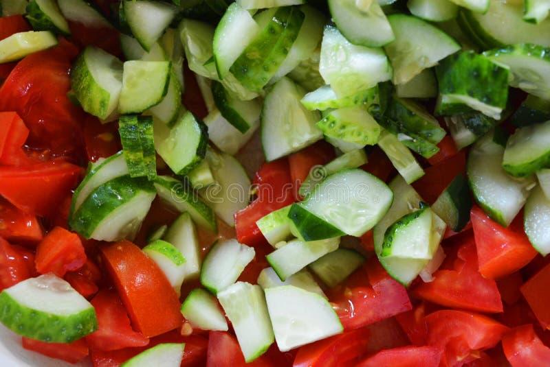 Verse gezonde groenten, kleine plakken van groene komkommers en rode tomaten voor de zomersalade, ingrediënten voor salade royalty-vrije stock foto
