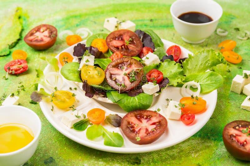 Verse gezonde mengelingssalade met tomaten, wilde kruiden, feta-kaas en vullingen op groene achtergrond, stock foto's