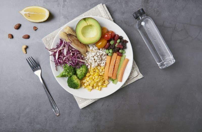 Verse gezonde plantaardige salade met wortel, graan, tomaat, avocado in plaat op lijstachtergrond met vrije tekstruimte voor diee royalty-vrije stock foto