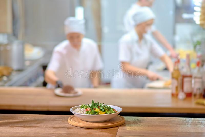 Verse gezonde salade op houten lijst Mening van hierboven met exemplaarruimte koks in de keuken als vage achtergrond erachter tek stock afbeeldingen