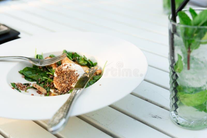 Verse gezonde salademaaltijd en mojitococktail op witte houten lijst bij openluchtrestaurant stock foto