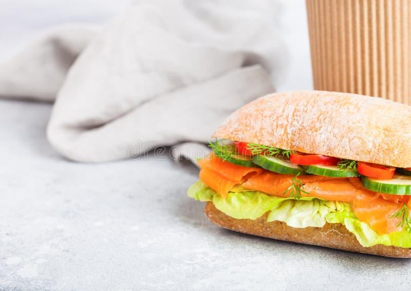 Verse gezonde zalmsandwich met sla en komkommer met document kop van koffie op witte steenachtergrond Ontbijtsnack ruimte royalty-vrije stock afbeeldingen
