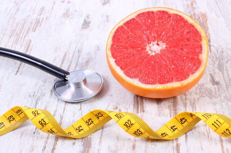 Verse grapefruit, centimeter en stethoscoop op oude houten achtergrond royalty-vrije stock foto's