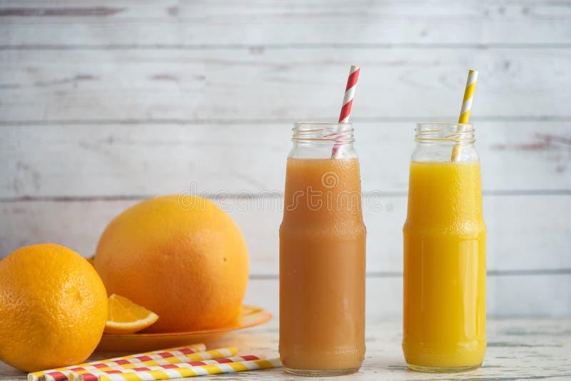 Verse grapefruits, sinaasappel en twee glazen grapefruit en jus d'orange op lichte houten lijst royalty-vrije stock fotografie