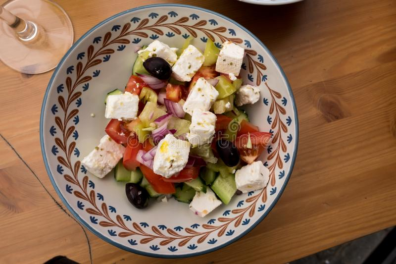 Verse Griekse Salade in aardewerkkom op houten lijst royalty-vrije stock foto