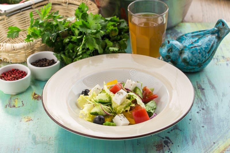 Verse Griekse salade met de kaaskomkommer van feta van de olijventomaat en ui op blauwe houten lijst stock afbeelding